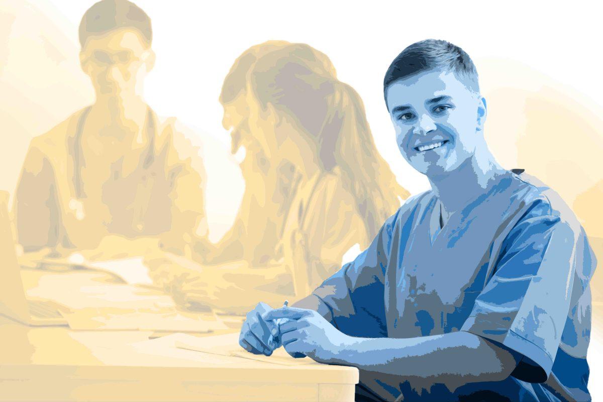 Pfleger lächelt und sitzt am Tisch mit Stift und Papier im Hintergrund besprechen Pflegekräfte