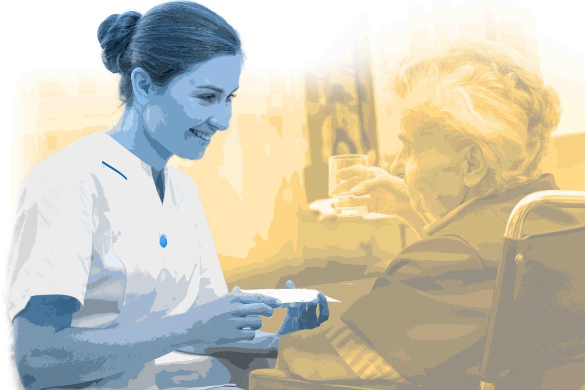 Pflegefachkraft überreicht älterer Dame die Medikamente